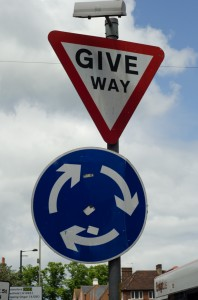"A ""give way"" sign over a roundabout sign."